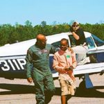 A middle school aged boy in cargo shorts and button up shirt walks with an experienced pilot discussing aviation and acedemic excellence on a flight line, as a crew memher gives a peace sign outside the parked airplane behind them.